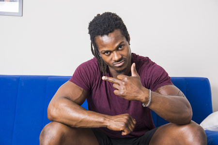 Handsome muscular black man sitting on couch at home, looking confident at camera