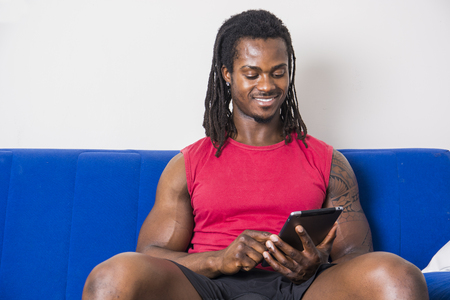 Handsome muscular black man sitting on couch at home, looking and using cell phone with cute smiling expression