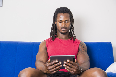 Handsome muscular black man watching movie on tablet PC, sitting on couch at home