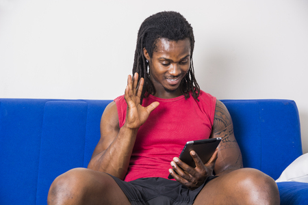 taking video: Handsome muscular black man sitting on couch at home doing videocall or videochat on cell phone, looking confident and waving with cute smiling expression