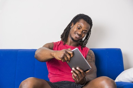 Handsome muscular black man playing videogame on tablet PC, sitting on couch at home Stock fotó