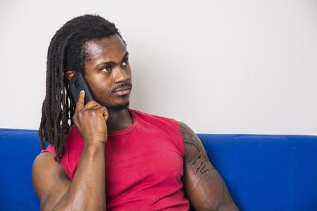 Jóképű izmos fekete ember ül a kanapén otthon, hívja és beszélget a mobiltelefon aranyos mosolygó kifejezést Stock fotó