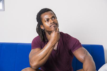 Szép, bizonytalan, bizonytalan fekete ember gondolkodott, kétségbeesett arckifejezéssel nézett fel Stock fotó