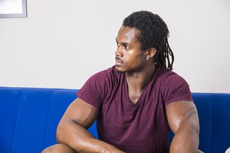 Jóképű izmos fekete férfi otthon ül a kanapén, és oldalra néz