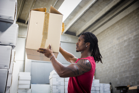 Black handsome muscular man working in warehouse, moving and handling cardboard boxes and organizing logistics