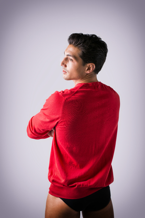 A young man with red wool sweater and underwear, back view, arms crossed on chest. Grey background