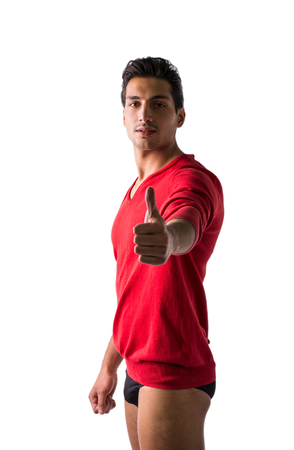 A young man with red wool sweater and underwear, front view, doing thumb up gesture. Isolated on white background Stock Photo