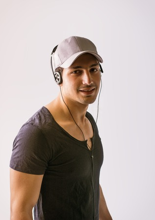 A young man with headphone listening to music looking at camera and smiling, on white background