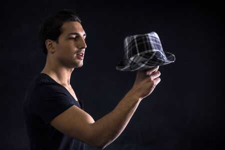 Young man with dark t-shirt holding black and white checkered hat on dark background