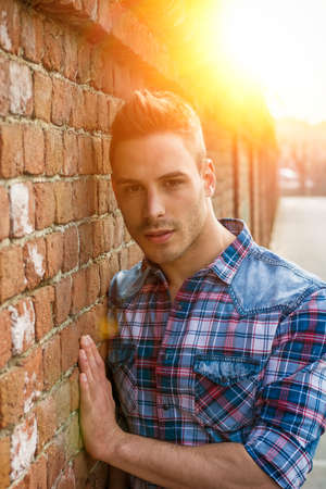 Smiling young man leaning on old brick wall, wearing blue and red shirt and jeans Stock fotó
