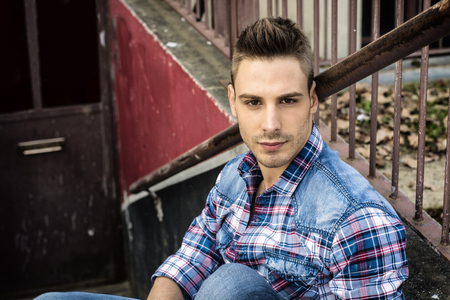 An attractive young man sitting on ground outdoor in public park against metal fence, wearing jeans and shirt Stock fotó