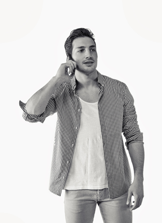 Jóképű, mosolygós fiatalember beszél a mobiltelefonján, elszigetelt fehér háttér műterem lövés. Keresek egy oldalsó