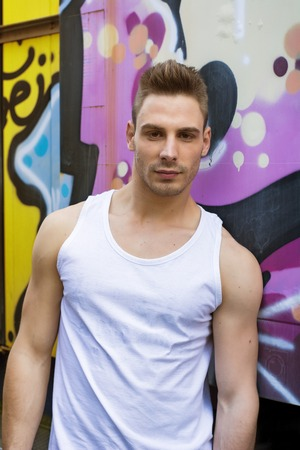 Young man against bright colored graffiti wall wearing white tanktop and looking at camera