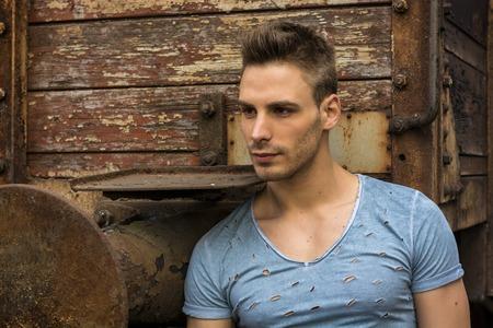 Fiatal, jóképű férfi ült a régi rozsdás vonaton. Kék t-shirt viselő kamerával Stock fotó