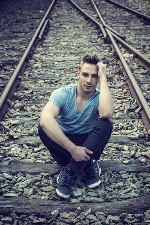 Vonzó fiatalember ült a vasút, kék t-shirt és farmer, néztem kamera