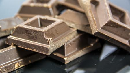 Pieces of dark chocolate bar on neutral background in studio shot Stock fotó