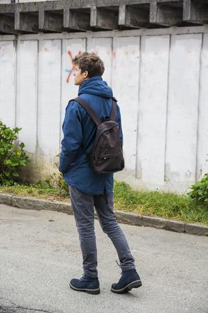 Tizenéves, fiú, egyedül sétálni a városban utcai hátizsák, hátulnézetből