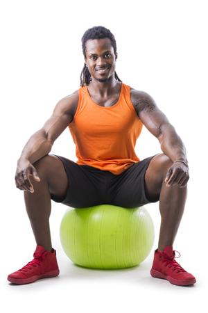 Izmos fekete ember ül felfújható fitness labda, nézi kamera, elszigetelt fehér háttér