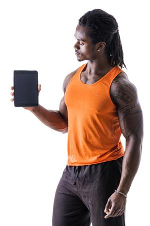 Jóképű fekete fiatalember tartja és mutatja tablet PC, álló elszigetelt fehér háttér, fárasztó sportruházat Stock fotó