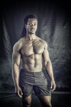 Afroamerikai testépítő férfi, meztelen izmos törzs, fehérnemű viselése, fekete háttérrel