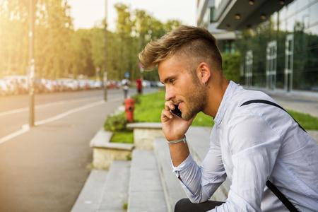 Stílusos, divatos, szőke fiatalember, aki mobiltelefonon beszél, az irodai ablak melletti kültéri, magabiztosan elnézve