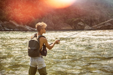 Young handsome male tourist standing and fishing in river in sunny day with rod Stock fotó