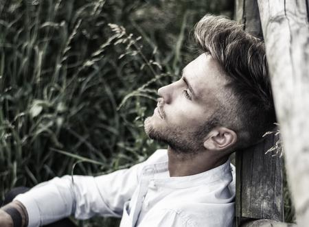 Szőke, kék szemű fiatalember támaszkodott a fa kerítés a fű gyep naplemente, gondolkodó, elnéző