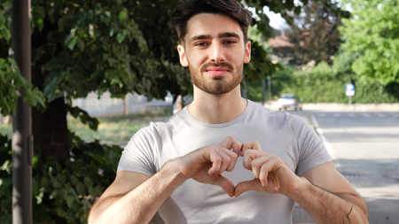 Handsome young man making heart sign with his hands and fingers. Outdoor in the street Standard-Bild