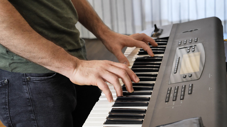 Side view of male musician playing electric piano or electronic keyboard or synthesizer at home. Stock fotó