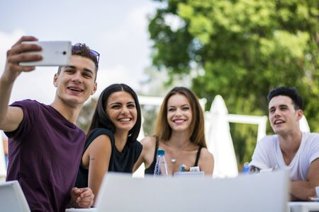 Young handsome men and attractive women smiling sitting at table making selfie.