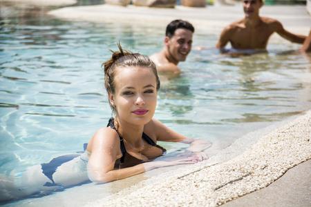 Young beautiful woman wearing bikini smiling looking at camera and men relaxing in pool.