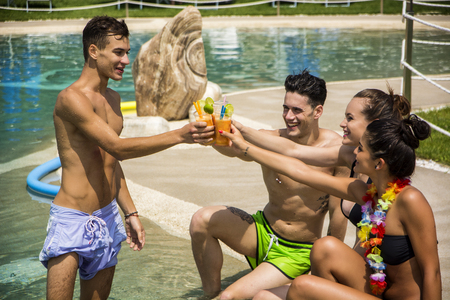 Young brunette men and women relaxing at pool smiling clinking with glasses tanning. Stock fotó