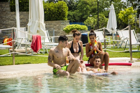 Young handsome man and attractive women in swimwear sitting at pool relaxing under sun. Stock fotó