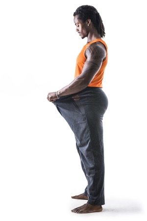 afroamerican: Black male bodybuilder has lost weight, wearing large pants and stretching them to see his progress