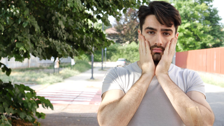 Young exhausted man holding hands on cheeks looking unhappily at camera on background of street. Stock fotó