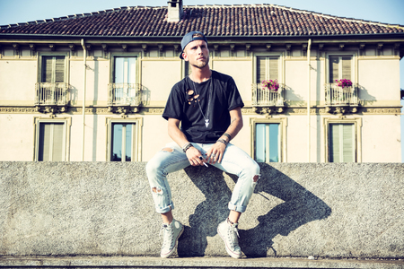 Young trendy hipster man in casual clothing posing on stone fence at street in sunlight looking away.