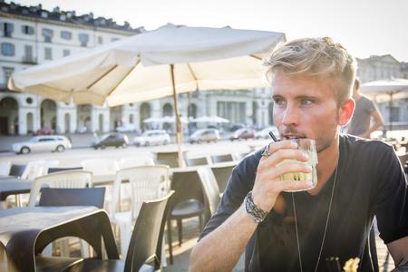 Szép szőke fiatal férfi ül Torinó kávézóban gazdaság üveg visel fekete póló látszó el.