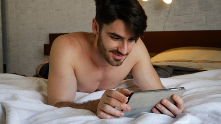 Young handsome man lying in bed and using tablet computer or reading an ebook in his bedroom at home at night