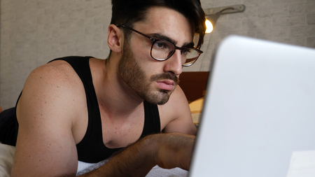 Attractive Young Man with Serious Expression, with Laptop on Bed Working on his Start-up Business - Young Male College or University Student Doing Homework, in Bedroom Stock fotó