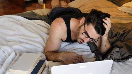 Attractive Young Man with Serious Expression, with Laptop on Bed Working on his Start-up Business, with Books Next to Him - Young Male College or University Student Doing Homework, in Bedroom