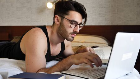 Attractive Young Man with Serious Expression, with Laptop on Bed Working on his Start-up Business, with Books Next to Him