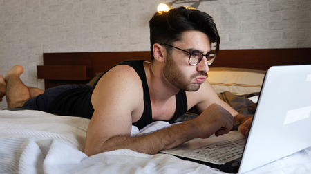 Tired, Fed-Up Young Man with Serious Expression, with Laptop on Bed Working on his Start-up Business - Young Male College or University Student Doing Homework, in Bedroom