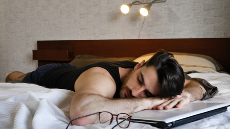 Bearded man lying on bed with eyes closed and having break while reading book and studying.