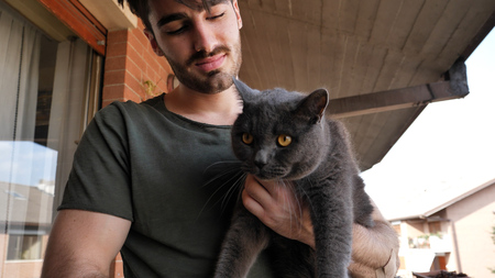 Handsome Young Animal-Lover Man Outside the House, Holding, Hugging and Petting his Gray Domestic Cat Pet. Stock fotó