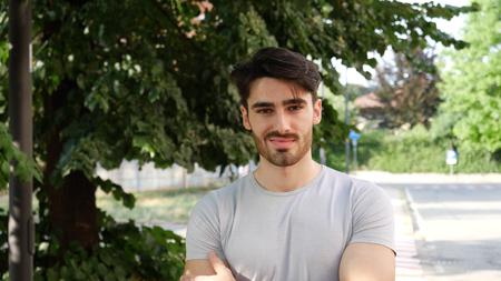 Jóképű fiatal férfi kültéri nézett körül, és a kamera a karok keresztbe a mellkas Stock fotó