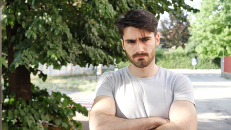 Handsome young man outdoor looking around and at camera with arms crossed on chest