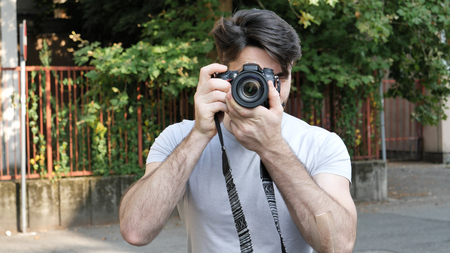 Handsome young male photographer taking photograph with professional photo camera hanging from his neck Stock fotó