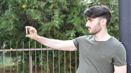 Young attractive man taking selfie photo outside in city street