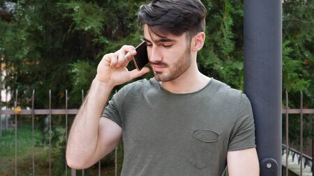 Young attractive man answering call on cellphone outside in city street