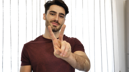 Attractive young man doing peace or victory sign with two fingers, indoor at home in his living-room